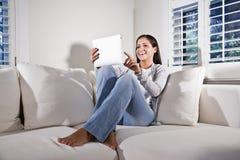 Spaanse vrouw die tabletcomputer op laag met behulp van stock afbeeldingen