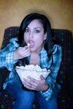 Spaanse vrouw met popcorn het letten op televisie royalty-vrije stock afbeelding