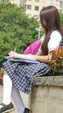 Spaanse Vrouwelijke Student Writing stock afbeeldingen