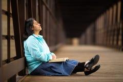 Spaanse Vrouwenzitting en het Mediteren van Bijbel op een Brug stock foto