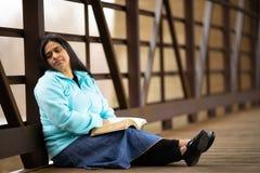 Spaanse Vrouwenzitting op een Brug en een Lezingsbijbel stock afbeeldingen