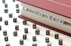 Spaanse woordconocimiento die die kennis betekenen met brieven wordt geschreven tussen een boek worden opgesloten dient en spreid stock foto