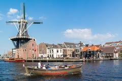 Spaarne-Fluss mit Kanalboot und Windmühle, Haarlem, die Niederlande Lizenzfreie Stockfotografie
