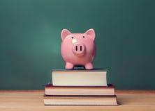 Spaarvarken bovenop boeken met bord die tot kosten van onderwijsthema leiden Stock Afbeeldingen