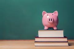 Spaarvarken bovenop boeken met bord, kosten van onderwijsthema Royalty-vrije Stock Foto's