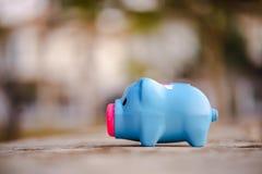 Spaarvarken buiten op huisachtergrond royalty-vrije stock afbeelding