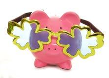 Spaarvarken die over met maat komedieglazen dragen Stock Foto's