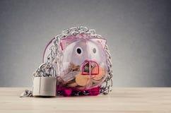 Spaarvarken door kettingen en hangslot wordt omringd op houten bureau dat royalty-vrije stock foto