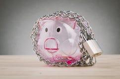 Spaarvarken door kettingen en hangslot wordt omringd op houten bureau dat royalty-vrije stock fotografie