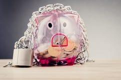 Spaarvarken door kettingen en hangslot wordt omringd op houten bureau dat royalty-vrije stock foto's