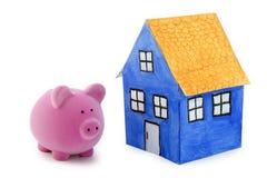 Spaarvarken en blauw document huis Stock Fotografie