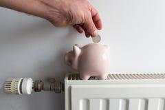 Spaarvarken en geld bij het verwarmen van radiator met temperatuurregelgever Royalty-vrije Stock Foto's