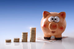 Spaarvarken en gestapelde muntstukken op witte glas blauwe achtergrond Royalty-vrije Stock Foto