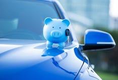 Spaarvarken en sleutel op een autokap royalty-vrije stock afbeeldingen