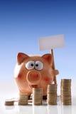 Spaarvarken met aanplakbord en gestapelde muntstukken blauwe achtergrond vert Royalty-vrije Stock Fotografie