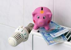Spaarvarken met de besparingsverwarmingskostennen van de radiatorthermostaat Stock Foto
