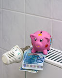 Spaarvarken met de besparingsverwarmingskostennen van de radiatorthermostaat Stock Fotografie