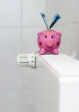 Spaarvarken met de besparingsverwarmingskostennen van de radiatorthermostaat Royalty-vrije Stock Fotografie