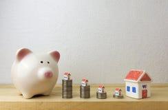 Spaarvarken met huis en muntstukken Royalty-vrije Stock Foto's