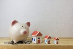 Spaarvarken met huis en muntstukken Stock Foto