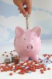 Spaarvarken met muntstukken en pillen Stock Foto