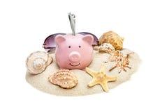 Spaarvarken met zeeschelpen, zonnebril en geld op stapel van zand Ge?soleerd op wit stock afbeeldingen