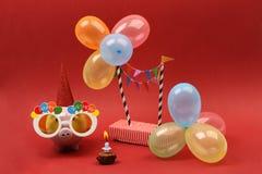 Spaarvarken met zonnebril Gelukkige verjaardag, partijhoed en multicolored partijballons op rode achtergrond Royalty-vrije Stock Foto's