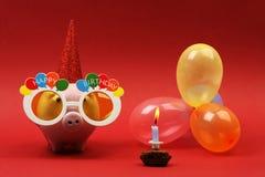 Spaarvarken met zonnebril Gelukkige verjaardag, partijhoed en multicolored partijballons op rode achtergrond Stock Foto's