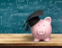 Spaarvarken met Zwarte Graduatiehoed op bord stock fotografie