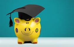 Spaarvarken met Zwarte Graduatiehoed op licht royalty-vrije stock afbeeldingen