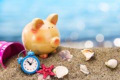 Spaarvarken op zand met de zomeroverzees Stock Foto