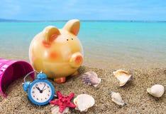 Spaarvarken op zand met de zomeroverzees Stock Foto's