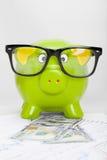 Spaarvarken over effectenbeursgrafiek met 100 dollarsbankbiljet Royalty-vrije Stock Foto's