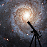 Space background with silhouette of telescope. Messier 74. NGC 628 Spiral galaxy in the constellation Pisces. Elements of this image are furnished by NASA stock photo