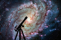 Space background with silhouette of telescope. Messier 83. Southern Pinwheel Galaxy, M83 in the constellation Hydra. Elements of this image are furnished by royalty free stock images