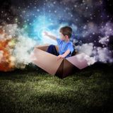 Space Boy in Box Touching Glowing Star. A young boy is sitting in a cardboard box and floating in the night sky reaching for a star in space stock photography