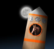 Space Boy in Cardboard Box Isolated on Black. A young boy is in a cardboard space rocket ship pretending to be an astronaut and looking at the moon in the night Stock Images