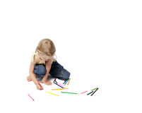 Space for creation. Little girl painting by coloured pencils sitting in big white space stock photo