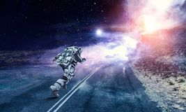 Running spaceman and galaxy. Mixed media. Space fantasy concept with running astronaut. Mixed media Stock Photography