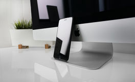 Space Gray Iphone 6 Laying on Silver Imac Royalty Free Stock Photos
