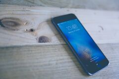 Space Gray Iphone on Wooden Surface Stock Photography