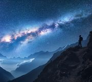 Space with Milky Way, girl and mountains at night. Space with Milky Way, girl and mountains. Silhouette of standing woman on the mountain peak, mountains and Royalty Free Stock Photo
