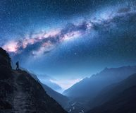 Space with Milky Way, girl and mountains at night. Space with Milky Way, girl and mountains. Silhouette of standing woman on the mountain peak, mountains and Royalty Free Stock Photos