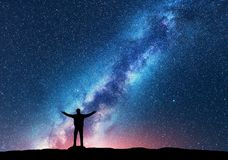 Space. Milky Way with silhouette of a happy man. Space. Milky Way with silhouette of a standing happy man with raised up arms on the hill. Night landscape with royalty free stock images