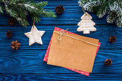 Space for new year greeting. Paper near christmas toys and spruce branches on blue wooden background top view mockup Royalty Free Stock Photography