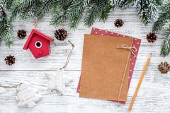 Space for new year greeting. Paper near christmas toys and spruce branches on light wooden background top view mockup Royalty Free Stock Photo