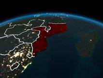 Mozambique on Earth at night. Space orbit view of Mozambique highlighted in red on planet Earth at night with visible country borders and city lights. 3D Royalty Free Stock Photo