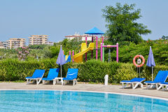 Space by pool with sun loungers. And childrens playground with slides royalty free stock photo