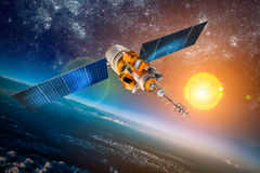 Space satellite over the planet earth. Space satellite orbiting the earth on a background star sun. Elements of this image furnished by NASA Stock Photo
