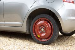 Space saver wheel. And spare tyre or tire fitted to a small car royalty free stock photos